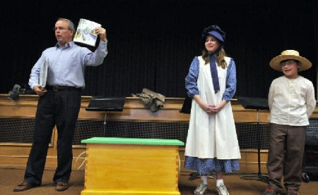 Dennis Scholl unveils a traveling trunk to a group of students (Photo by Times Leader)